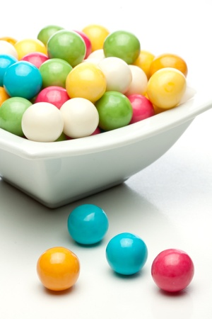 many colored gumballs on a white background photo