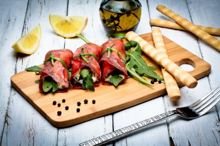 bresaola rolls with ricotta cheese and arugola photo