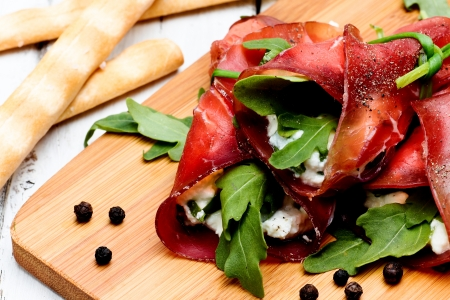 bresaola rolls with ricotta cheese and arugola Stockfoto