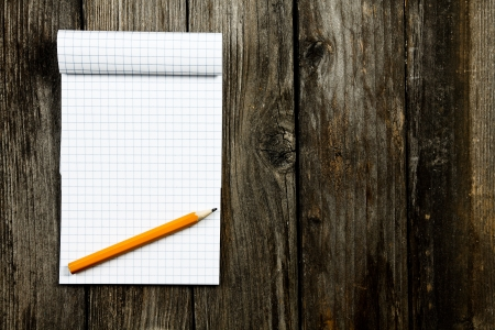 notepad and pencil on a wooden planks Фото со стока