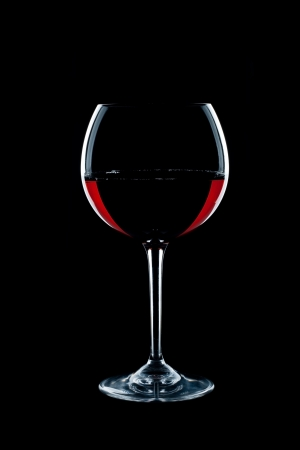 a glass of red vine on black background