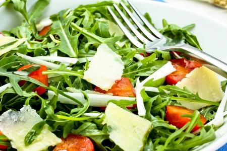 salad with arugula, cherry tomatoes, parmesan and shallot Фото со стока
