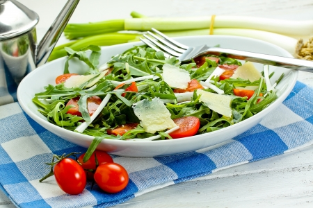 salad with arugula, cherry tomatoes, parmesan and shallot Фото со стока