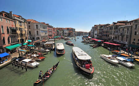 The view from the Rialto Bridge on the Grand Canal Venice. With Gondolas, Vaperettos and water taxis creating a busy scene. photo