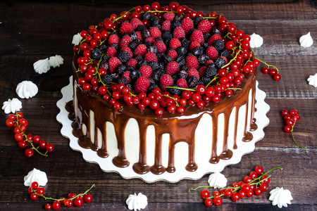 cake with red currants, raspberries and blackberries on a wooden background
