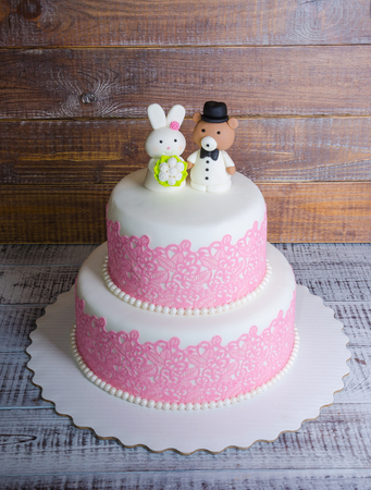 two-tier fondant wedding lace cake with bear and bunny Stock Photo