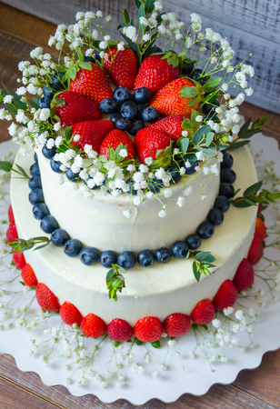 two-tier cream cheese wedding cake with blueberries and strawberries