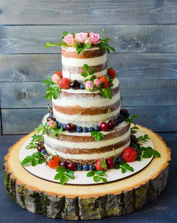 果実や花で飾られた裸のウェディング ケーキ