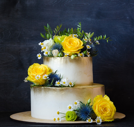 Two layered gilded wedding cake with flowers Stock Photo