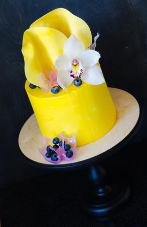 Yellow cream cake with orhid and chocolate twist Stock Photo