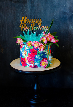 Tropical birthday cake on a cakestand with a topper