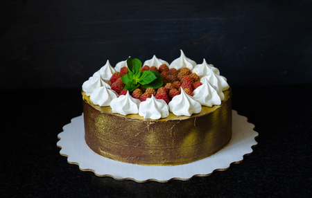 gilded chocolate cake with merengues, raspberries and mint leaves