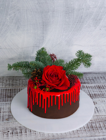 New year color drip chocolate cake with red roses and fur tree