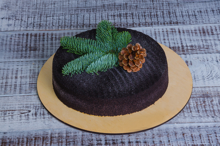 Christmas chocolate velvet cake decorated with pinecone on wood