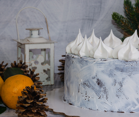 chocolate christmas cake decorated with merengues on wooden background