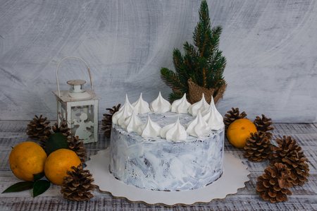 chocolate cristmas cake decorated with merengues on wooden background Stock Photo