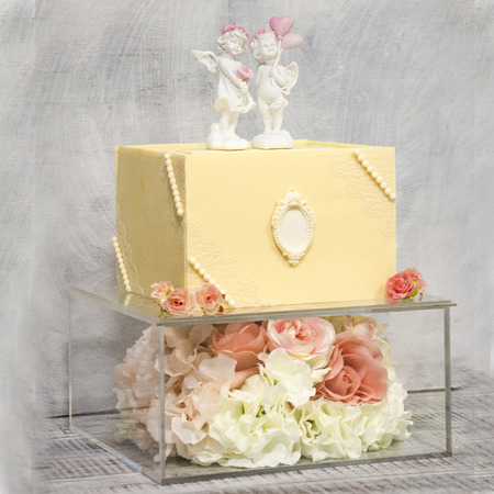 Exquisite two tiered chocolate wedding cake on glass box decorated with roses Stock Photo