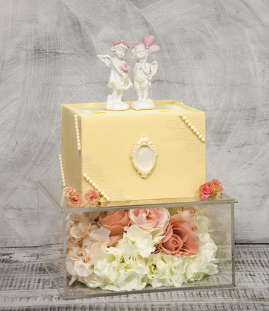 Exquisite chocolate wedding cake on glass box decorated with roses