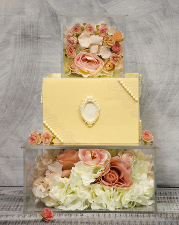 Exquisite three tiered chocolate wedding cake on glass box decorated with roses Stock Photo
