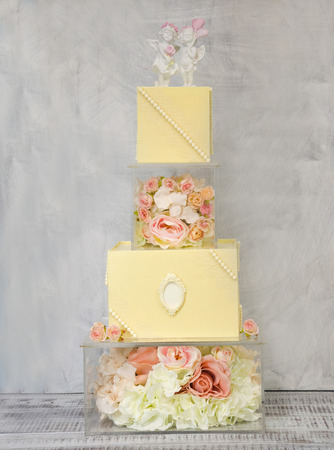 Exquisite four tiered chocolate wedding cake on glass box decorated with roses Stock Photo