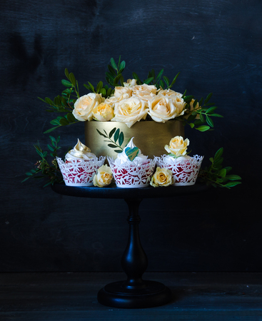 a Gentle wedding cake in golden chocolate box with yellow roses and pistachio Stock Photo