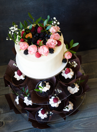 a Cream cheese wedding cake with cupcakes decorated with berries and flowers