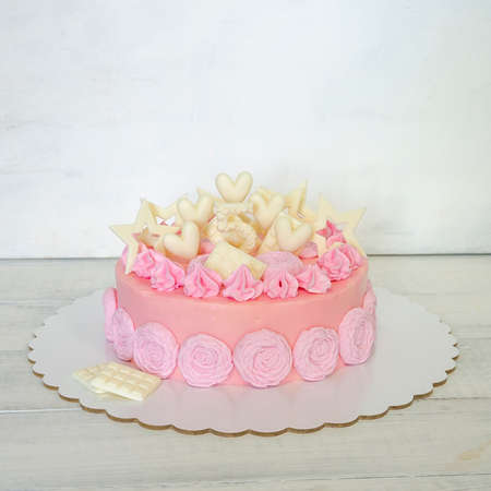 A pink creamchease cake with flowers for 5 year birhtday