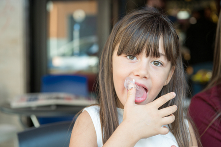 finger in mouth: small little girl licks his fingers made of ice cream