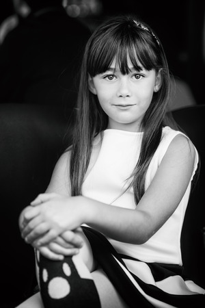 decided: little girl posing as Audrey Hepburn style, decided and sure.