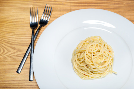 kilos: spaghetti with garlic, oil and hot peppers with parsley and fork on table