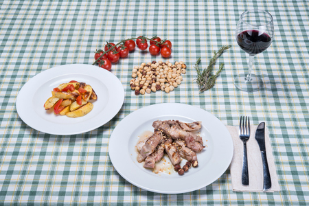 Cut pork with rosemary, cherry tomatoes and potatoes Stock Photo