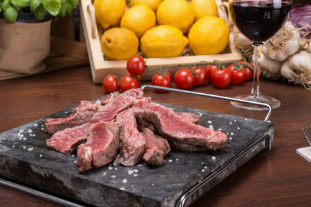 Sirloin of local veal on italian table with lemon, wine, fork and cheese