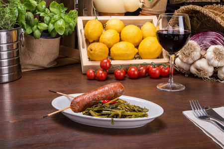 Two sausages and broccoli on italian table Stock Photo