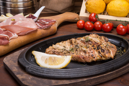 Leg of roasted chicken on italian table and lemon