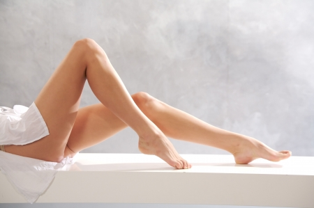 woman legs: beautiful legs on white bench Stock Photo