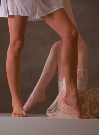 girl soles: beautiful pair of legs on white bench Stock Photo