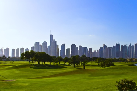 city people: Bright green solar golf course with skyscrapers on the horizon