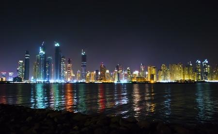 jachthaven: Nachtscène op de brandende wolkenkrabbers van Dubai tot uiting in het water van de Perzische Golf