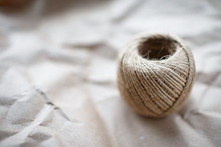 A ball of twine on a crumpled  paper