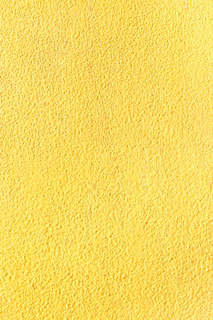 Bright yellow background. Painted plastered wall. Desktop wallpapers or texture.