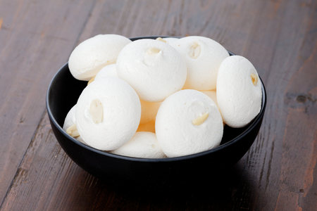 White meringues on a black plate on a wooden background. Meringues with peanuts.