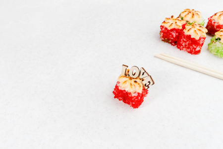 Sushi Valentines Day. Love sushi rolls. Sushi rolls, chopsticks and the inscription love on a light background.