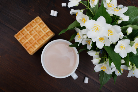 Romantic breakfast. Bouquet of jasmine. A cup of hot cocoa and Viennese waffles.