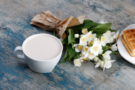 Romantic breakfast. Bouquet of jasmine. A cup of hot cocoa and Belgian waffle.