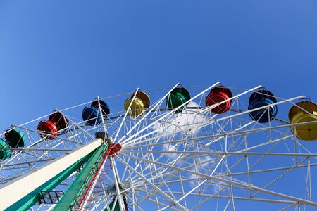 Ferris wheel against the blue sky. Multi-colored cabins. Attraction in the park. Stock fotó