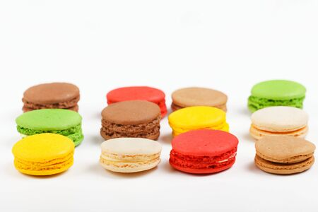 Macarons on a white background. Multicolored sweet macarons laid out in rows.