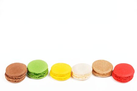 Macarons isolated on white background. Colored macaroons lined up in a row. On top of the copy space.