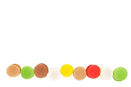 Macarons isolated on white background. Colored macaroons lined up in a row. Top view, save space. Imagens