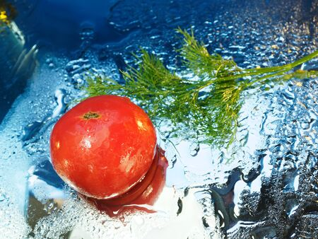Tomato and dill on a mirror background. View from above. Wet vegetables.