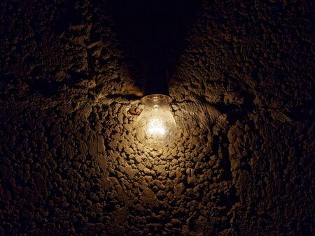 Light bulb on a dark rough stone background. Gloomy dark background.